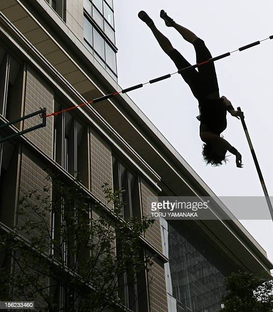 Japanese polevaulter Takehito Ariki clears a bar beside a building during his performance on the street at Marunouchi business and shopping district...