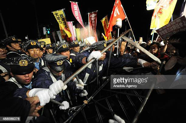 Japanese police officers intervene protesters during a rally against Japan Security Bills in front of the National Diet building in Tokyo Japan on...
