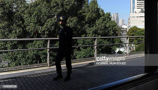 A Japanese policeman keeps an eye on commuters on a foot over bridge near the venue ahead of the AsiaPacific Economic Cooperation forum in Yokohama...