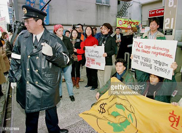 A Japanese policeman looks on as environmental group members from 10 countries stage a sitin and a 'human chain' to protest against American oil...