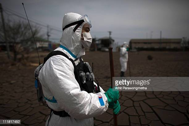 Japanese Policeman wearing a protective suit stands guard as search for tsunami victims continues within the exclusion zone about 12 miles away from...