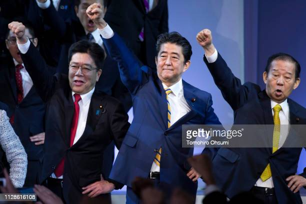Japanese Prime Minister and Liberal Democratic Party President Shinzo Abe raises his arm with other party members at the party's annual convention on...