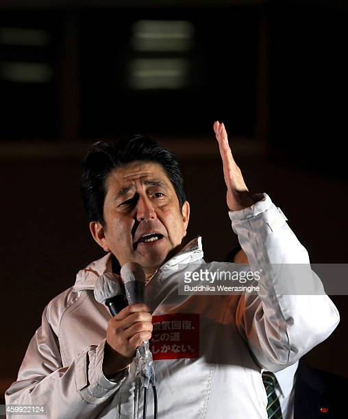 Japanese Prime Minister and president of the Liberal Democratic Party Shinzo Abe speaks to voters from the roof of a campaign bus during an election...