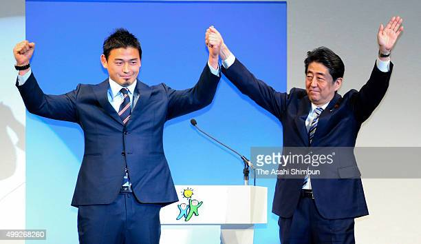 Japanese Prime Minister and President of the ruling Liberal Democratic Party Shinzo Abe and guest Ayumu Goromaru rise their fists during the 60th...