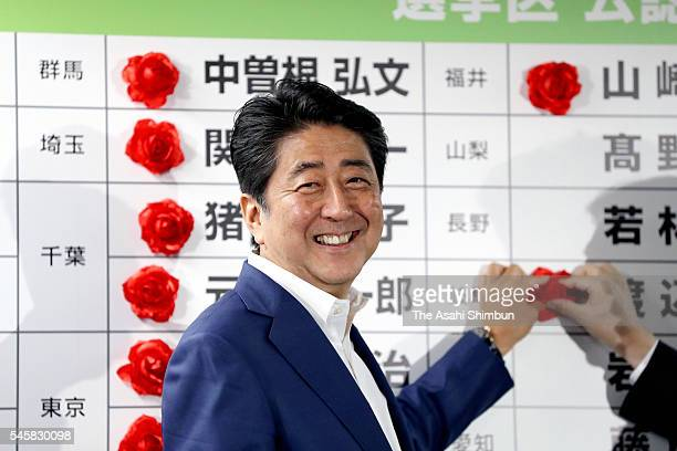 Japanese Prime Minister and ruling Liberal Demcratic Party President Shinzo Abe smiles while placing a paper rose on names of his party's winning...