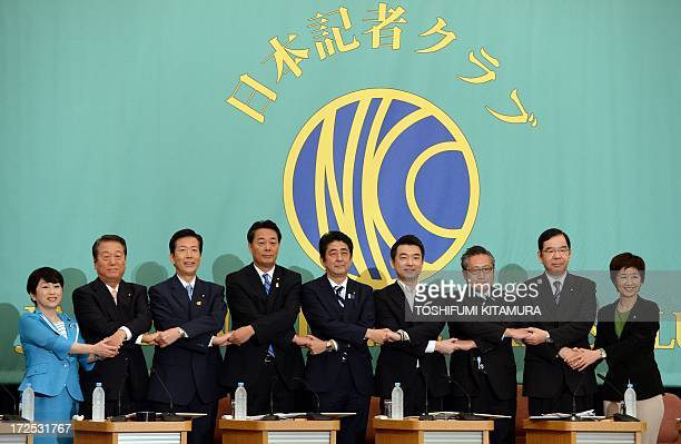 Japanese Prime Minister and ruling Liberal Democratic Party leader Shinzo Abe shakes hands with Democratic Party of Japan leader Banri Kaieda and...