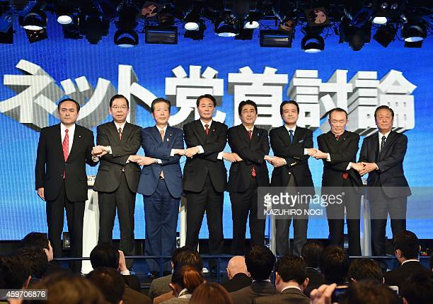 Japanese Prime Minister and ruling Liberal Democratic Party leader Shinzo Abe shakes hands with seven other party leaders at a political debate for...