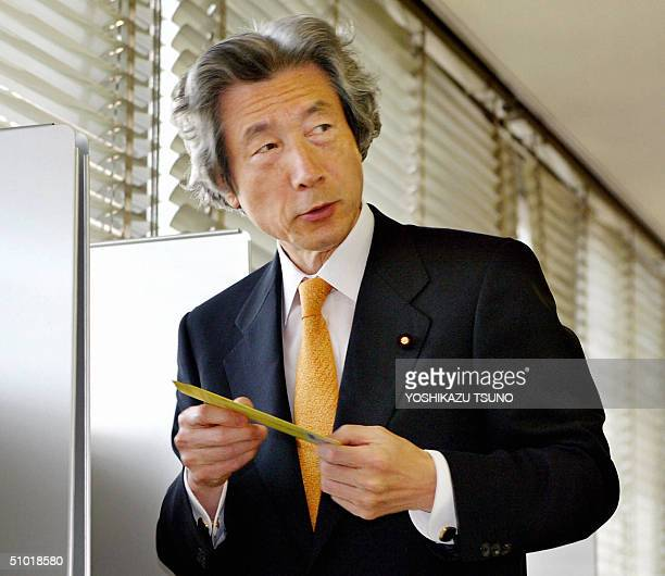 Japanese Prime Minister and ruling Liberal Democratic Party leader Junichiro Koizumi holds his absentee voting paper for the 11 July Upper House...