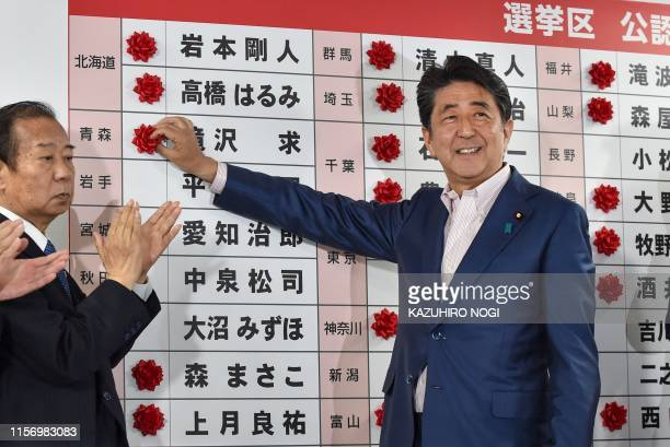 TOPSHOT Japanese Prime Minister and ruling Liberal Democratic Party president Shinzo Abe attaches paper flowers on the winning candidates of the...