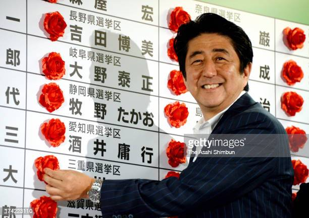 Japanese Prime Minister and ruling Liberal Democratic Party president Shinzo Abe places paper flowers to candidates who won seats at the LDP...