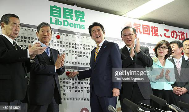 Japanese Prime Minister and ruling Liberal Democratic Party president Shinzo Abe places a paper flower on his name to celebrate his win at the LDP...
