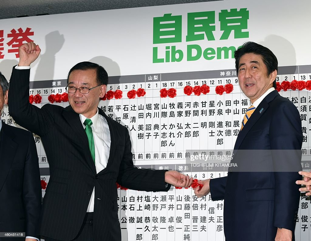 Japanese Prime Minister and ruling Liberal Democratic Party (LDP) president Shinzo Abe (R) smiles as he points to a flower pinned next to his name in the candidates list board as LDP Secretary-General Sadakazu Tanigaki (L) gestures at the party headquarters in Tokyo on December 14, 2014. Japanese Prime Minister Shinzo Abe won comfortable re-election December 14 in a snap poll he had billed as a referendum on his economic policies after early success faded into a recession.