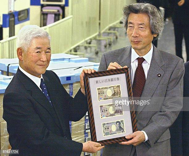 Japanese Prime Minister Junichiro Koizumi and Bank of Japan governor Toshihiko Fukui shows the new design of Japanese yen notes of 10 5000 and 1000...