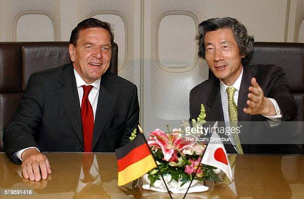 Japanese Prime Minister Junichiro Koizumi and German Chancellor Gerhard Schroder talk in the plane on the way to Japan on June 28 2002 in flight