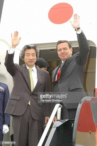 Japanese Prime Minister Junichiro Koizumi and German Chancellor Gerhard Schroder wave on departure for Japan at the Calgary International Airport on...