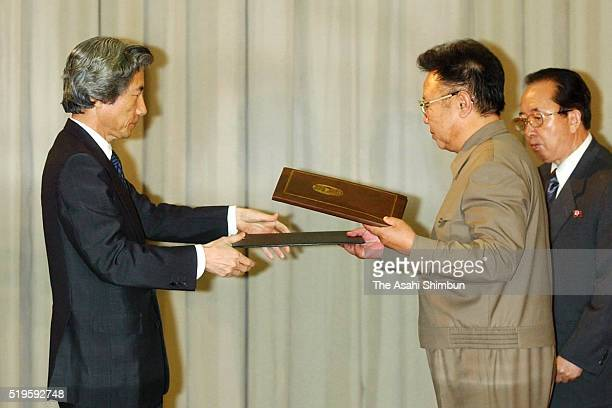 Japanese Prime Minister Junichiro Koizumi and North Korean leader Kim Jongil exchange the documents after signing the Pyongyang Declaration following...