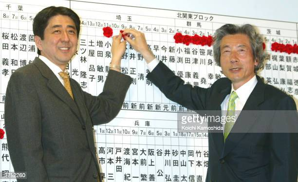 Japanese Prime Minister Junichiro Koizumi and Secretary General Shinzo Abe place a flower on the nameboard of the candidate who has been announced to...