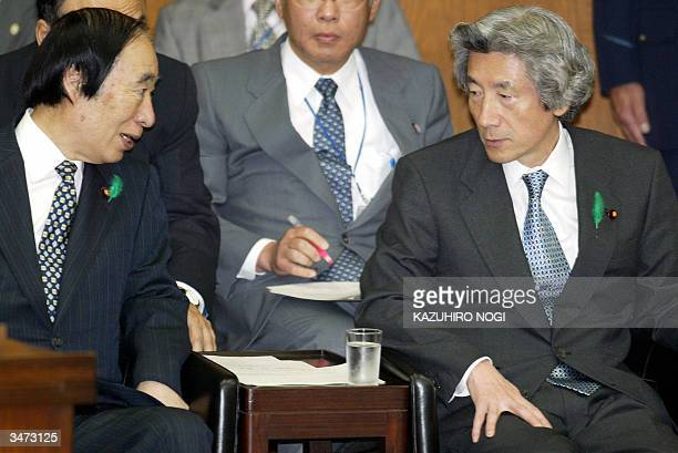 Japanese Prime Minister Junichiro Koizumi chats with Health Labor and Welfare Minister Chikara Sakaguchi during a committee session for...