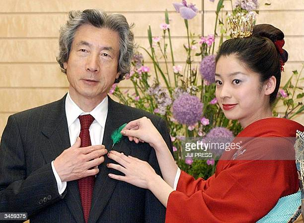 Japanese Prime Minister Junichiro Koizumi is all smiles as Japan's Cherry Blossom Queen Eriko Sawamura puts a green feather pin on the lapel of his...