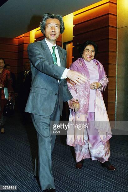 Japanese Prime Minister Junichiro Koizumi leads Indonesian President Megawati Soekarnoputri by hand before the start of JapanIndonesia Summit meeting...