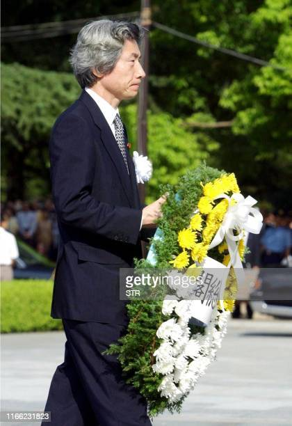 Japanese Prime Minister Junichiro Koizumi offers a flower wreath to the altar of the atomic bomb Abomb victims during the 57th Hiroshima Peace...