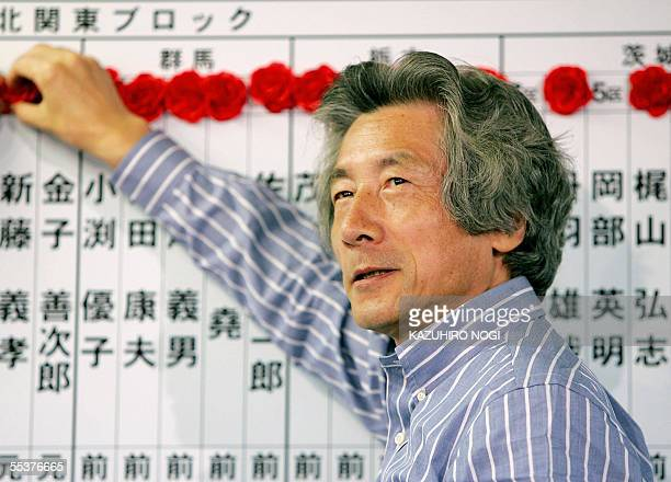 Japanese Prime Minister Junichiro Koizumi smiles as he puts a rosette on the name of an elected party member at the headquarters of the ruling...