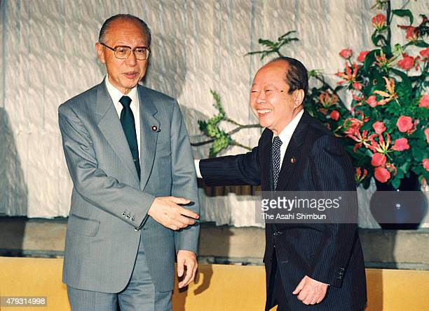 Japanese Prime Minister Kiichi Miyazawa shakes hands with opposition Japanese Socialist Party chair Makoto Tanabe during their meeting at Miyazawa's...