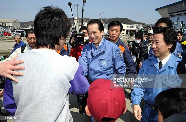 Japanese Prime Minister Naoto Kan shakes hands with the earthquake and tsunami survivors at Ishinomaki Port on April 10 2011 in Ishinomaki Miyagi...