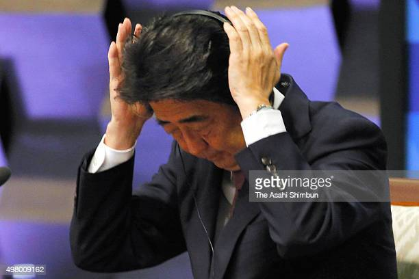 Japanese Prime Minister Shinzo Abe adjusts a headset during a plenary session of the Asia Pacific Economic Cooperation on November 19, 2015 in...
