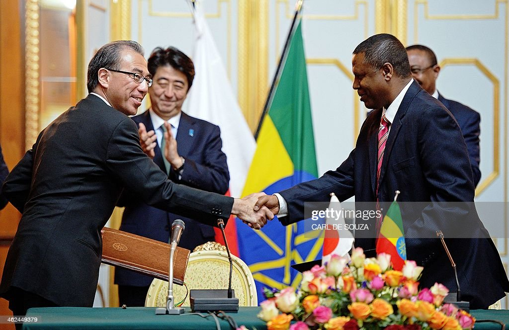 Japanese Prime Minister Shinzo Abe (2nd L) and Ethiopian Prime Minister Hailemariam Desalegn (back R) look on as unidentified delegates from Japan (L) and Ethiopia shake hands after signing an agreement for a new direct flight route between Japan and Ethiopia at the Ethiopian State House in Addis Ababa on January 13, 2014. Abe is on the final stop of a tour of Africa that has already taken him to Ivory Coast and Mozambique, hoping to boost ties and business relations on a continent that has become a key trading partner with China. AFP PHOTO / Carl de Souza