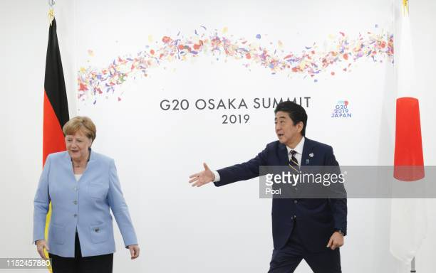 Japanese Prime Minister Shinzo Abe and German Chancellor Angela Merkel at their bilateral meeting on the first day of the G20 summit on June 28, 2019...