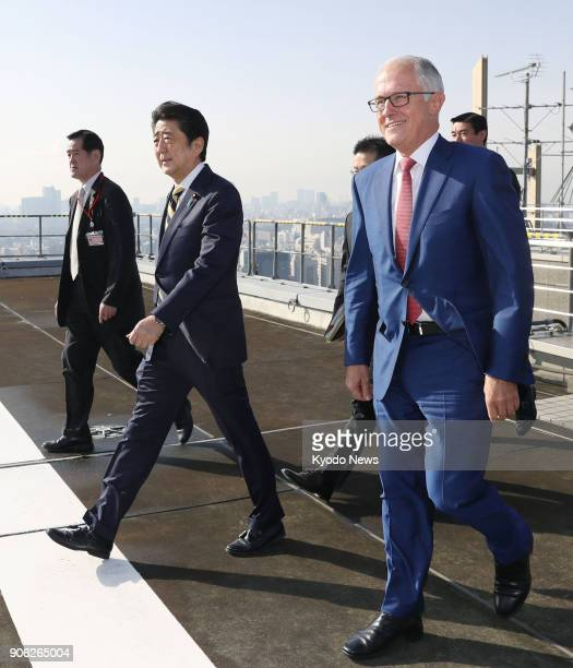 Japanese Prime Minister Shinzo Abe and his Australian counterpart Malcolm Turnbull walk on the roof of a Defense Ministry building in Tokyo on Jan 18...
