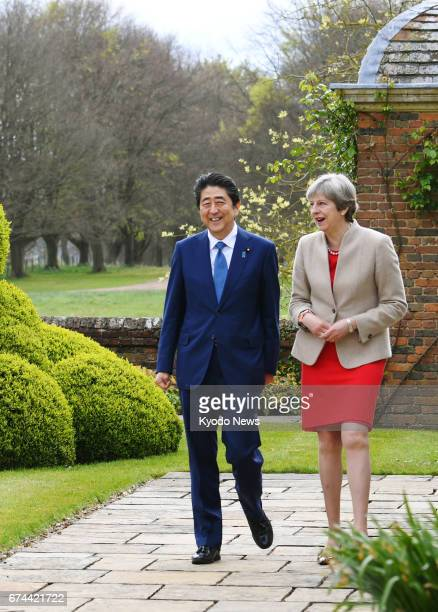 Japanese Prime Minister Shinzo Abe and his British counterpart Theresa May stroll the garden at the British prime minister's country residence near...