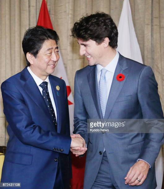Japanese Prime Minister Shinzo Abe and his Canadian counterpart Justin Trudeau shake hands before talks in Danang Vietnam on Nov 10 on the sidelines...