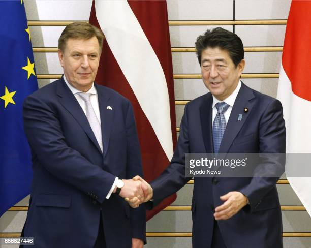 Japanese Prime Minister Shinzo Abe and his Latvian counterpart Maris Kucinskis shake hands before talks in Tokyo on Dec 6 2017 The two agreed to work...