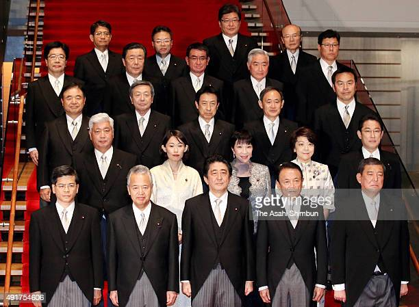 Japanese Prime Minister Shinzo Abe and his new cabinet members pose for photographs as he reshuffles his cabinet at his official residence on October...