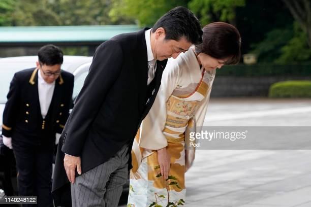 Japanese Prime Minister Shinzo Abe and his wife Akie Abe bow as they arrive for Emperor Akihito's abdication ceremony at the Imperial Palace on April...
