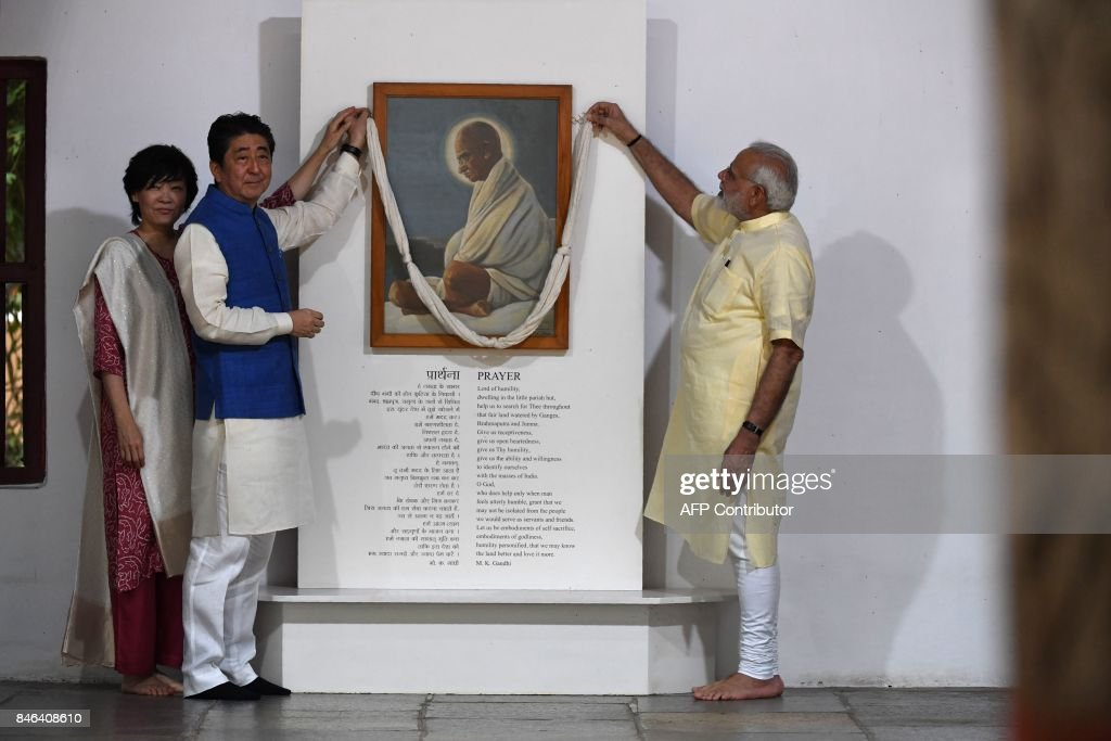 Japanese Prime Minister Shinzo Abe (C) and his wife Akie Abe pay their respects to Mahatma Gandhi along with Indian Prime Minister Narendra Modi (R) during their visit to Sabarmati Ashramand in Ahmedabad on September 13, 2017. India's premier Narendra Modi and Japanese counterpart Shinzo Abe are preparing to break ground on India's first bullet train project September 14, during an official visit to India by the Japanese prime minister. /