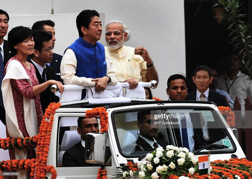 Japanese Prime Minister Shinzo Abe (C) and his wife Akie Abe (L) ride atop a vehicle with Indian Prime Minister Narendra Modi (R) as they arrive to visit to Sabarmati Ashramand in Ahmedabad on September 13, 2017. India's premier Narendra Modi and Japanese counterpart Shinzo Abe are preparing to break ground on India's first bullet train project September 14, during an official visit to India by the Japanese prime minister. /