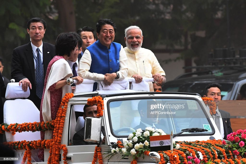 Japanese Prime Minister Shinzo Abe (C) and his wife Akie Abe (L) ride atop a vehicle with Indian Prime Minister Narendra Modi (R) as they arrive to visit Sabarmati Ashramand in Ahmedabad on September 13, 2017. India's premier Narendra Modi and Japanese counterpart Shinzo Abe are preparing to break ground on India's first bullet train project September 14, during an official visit to India by the Japanese prime minister. /