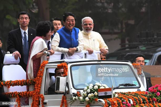 Japanese Prime Minister Shinzo Abe and his wife Akie Abe ride atop a vehicle with Indian Prime Minister Narendra Modi as they arrive to visit...