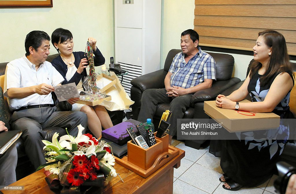 Japanese Prime Minister Shinzo Abe (1st L) and his wife Akie (2nd L) exchange gifts with Philippines President Rodrigo Duterte (2nd R) and his wife Honeylet Avancena (1st R) prior to the breakfast at Duterte's private residence on January 13, 2017 in Davao City, Philippines. Abe is on 6-day tour to the Philippines, Australia, Indonesia and Vietnam.