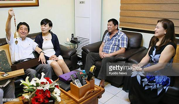 Japanese Prime Minister Shinzo Abe and his wife Akie receive a gift from Philippine President Rodrigo Duterte on Jan 13 during their visit to the...