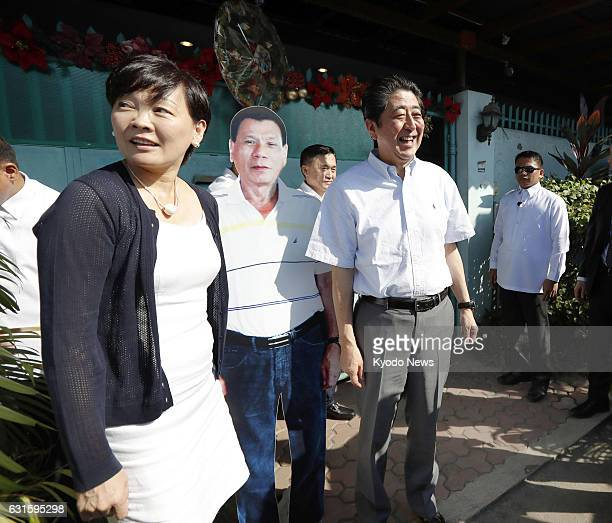 Japanese Prime Minister Shinzo Abe and his wife Akie stand between a lifesized picture of Philippine President Rodrigo Duterte on Jan 13 in front of...