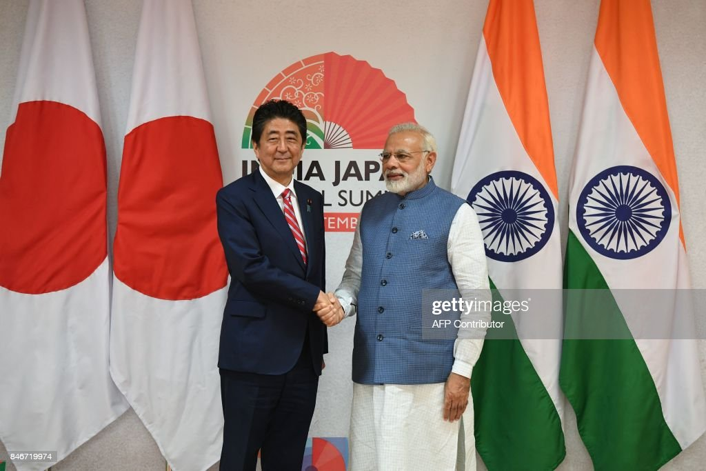 Japanese Prime Minister Shinzo Abe (L) and Indian Prime Minister Narendra Modi shake hands prior to a bilateral meeting and agreement signing during the India-Japan summit at Mahatama Mandir in Ahmedabad on September 14, 2017. India's first bullet train project, a $19-billion initiative linking Ahmedabad to Mumbai, was launched September 14 as Indian Prime Minister Narendra Modi and Japanese counterpart Shinzo Abe hailed fast-growing ties between Asia's two biggest democracies. SINGH