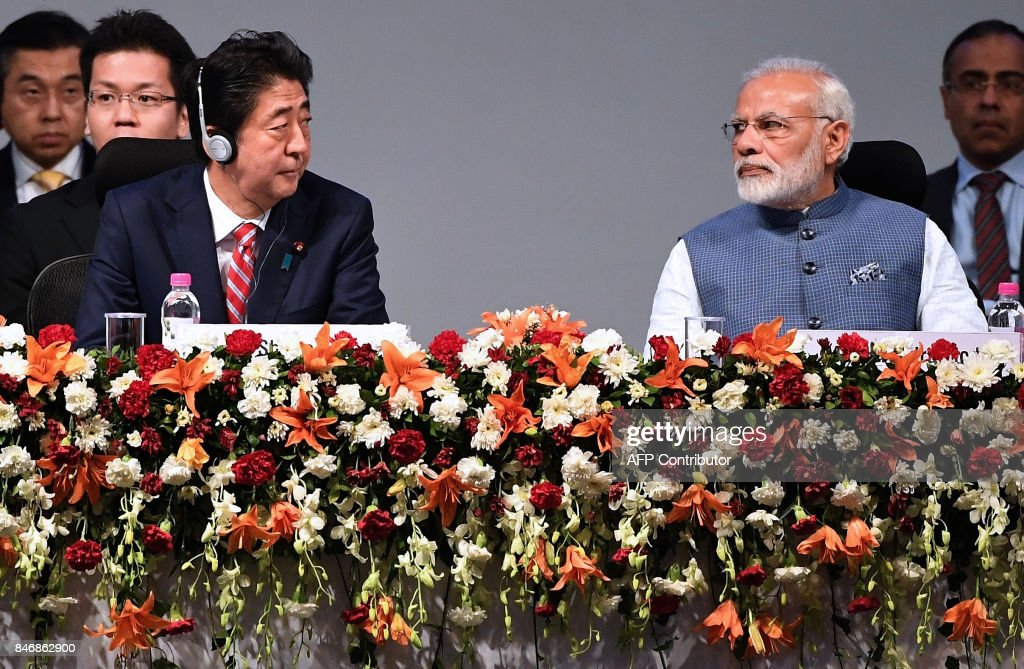 Japanese Prime Minister Shinzo Abe (L) and Indian Prime Minister Narendra Modi listens to a speaker during the India-Japan Buissness Plenary session at the India-Japan Annual summit at Mahatama Mandir convention center in Gandhinagar on September 14, 2017. Japan's Prime Minister Abe on September 14 inaugurated India's first bullet train project -- a $19 billion line in the home state of Indian leader Modi intended to revitalise the country's vast but dilapidated network. /