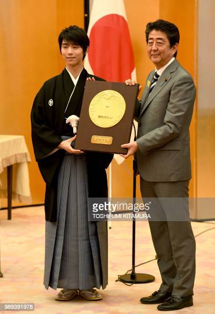 Japanese Prime Minister Shinzo Abe and Japanese figure skater Yuzuru Hanyu pose with People's Honor Award trophy during its presentation ceremony at...