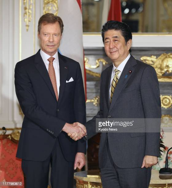 Japanese Prime Minister Shinzo Abe and Luxembourg Grand Duke Henri shake hands at the state guesthouse in Tokyo on Oct 25 2019