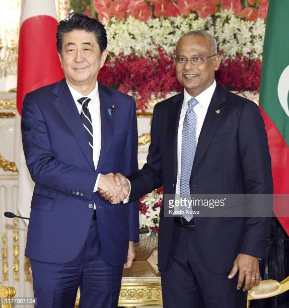 Japanese Prime Minister Shinzo Abe and Maldivian President Ibrahim Mohamed Solih shake hands at the state guesthouse in Tokyo ahead of their talks on...