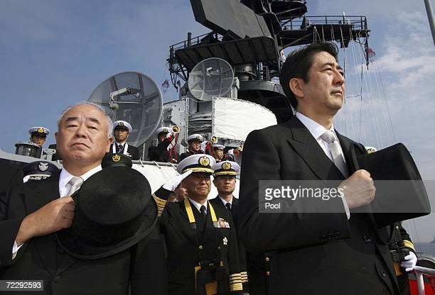 Japanese Prime Minister Shinzo Abe and Minister of State for Defense Fumio Kyuma salute during a Fleet Review of the Japan Maritime SelfDefense Force...
